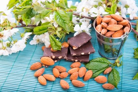 Almonds in a backet with pieces of chocolate with nuts scattered over blue bamboo overlay photo
