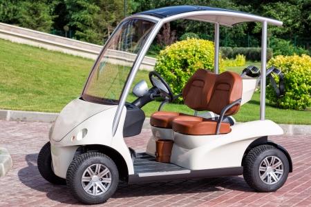 Electric golf cart near golf field