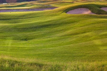 Perfect wavy ground with nice green grass on a golf field photo