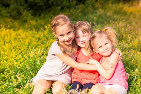 Happy smiling little kids outdoor in the park in summertime photo