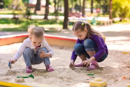Šťastné malé holčičky si hrají v sendbox na hřišti