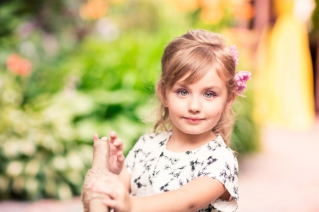Charming little girl in a beautiful dress in a park outdoor Stock Photo