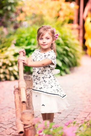 Charming little girl in a beautiful dress in a park outdoor photo