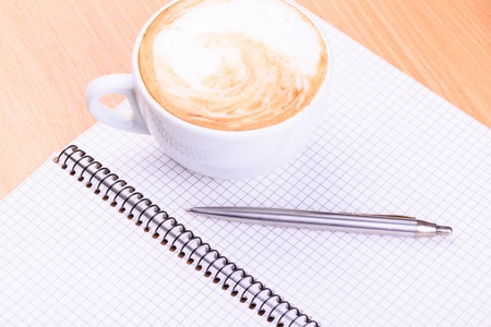 Open blank note book with coffee cup and a pen on wood table photo