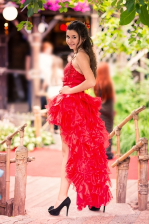 Beautiful girl in a gorgeous red dress in a park outdoor photo