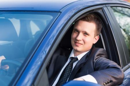 Pohledný mladý podnikatel sedí ve svém novém autě Reklamní fotografie
