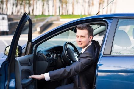Pohledný mladý podnikatel sedí v jeho novém autě