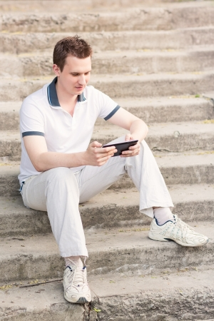 Young man sitting on a stairs with tablet pc outdoor photo