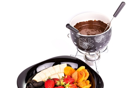 Chocolate fondue with fruits isolated on white background photo