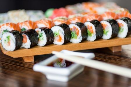 Sushi podávané na dřevěné desce v restauraci Reklamní fotografie