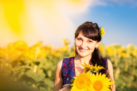 Young beautiful woman with a bouquet of sunflowers in the field Reklamní fotografie - 20993758