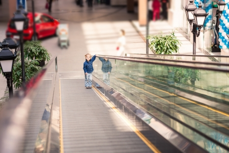 view of a staircase in a shop: Cute little child in shopping center on moving escalator Stock Photo