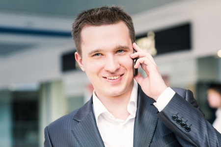 Handsome young successful businessman talking on his mobile photo