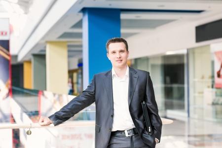 Pohledný mladý a úspěšný podnikatel v nákupním centru