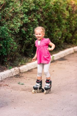 Little girl skating on roller skates at park, first attempt photo