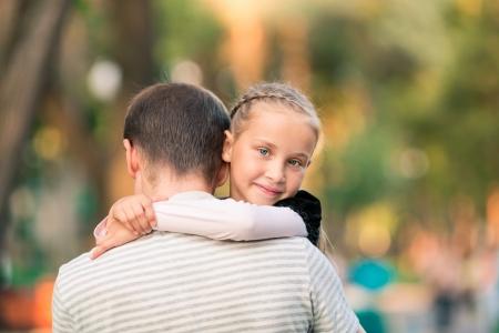 Šťastný úsměv mladý otec a dcera hraje v parku Reklamní fotografie