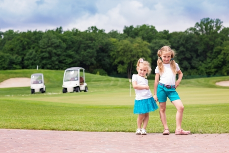 Cute little sportive gilrs on the golf course photo