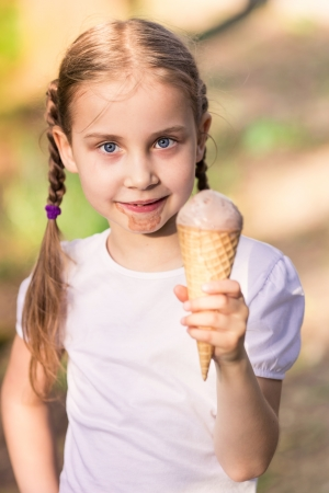 Happy cute child eating ice cream outdoor photo