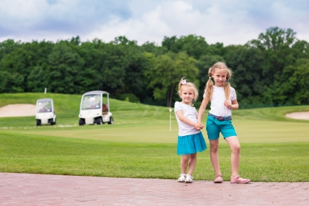 Cute little gilrs deportivas en el campo de golf photo