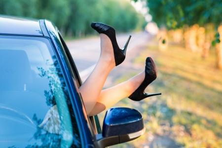 Ženské nohy v vysoký podpatek boty z v okně auta venkovní Reklamní fotografie