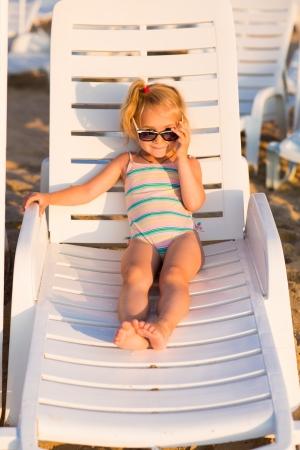 klein meisje op strand: Aanbiddelijk jong geitje in zonnebril zonnebaden op een lounge op een strand
