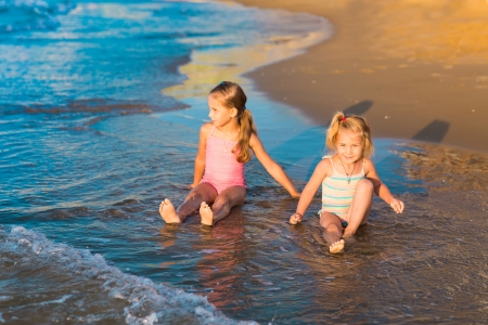 Two happy adorable kids playing in the sea on a beach photo
