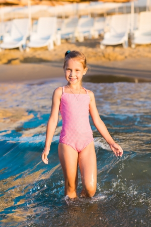 swimsuits: Adorable ni�a feliz jugando en el mar en una playa
