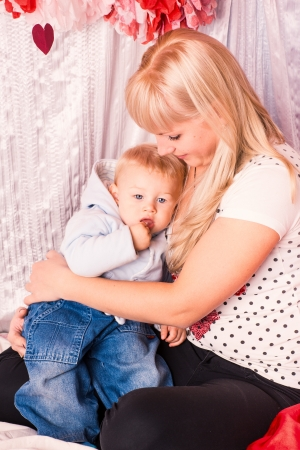 adult breastfeeding: Beautiful happy mother hugging a baby on a bed in the bedroom Stock Photo