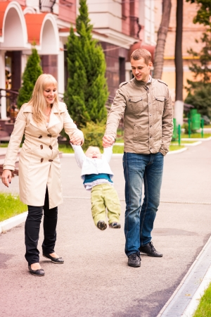 Happy family walking with a baby outdoor photo