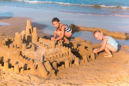Rozkošný holčičky vytvářející sandcastlle na pobřeží