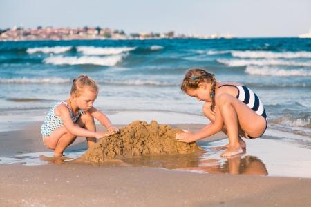 Rozkošný holčičky buduje sandcastlle na pobřeží