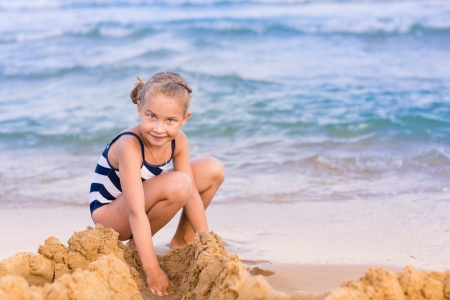 Adorable little girl building a sandcastlle at the seashore photo