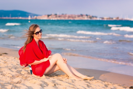 Beautiful woman with red scarf on the beach. Travel and vacation concept. photo