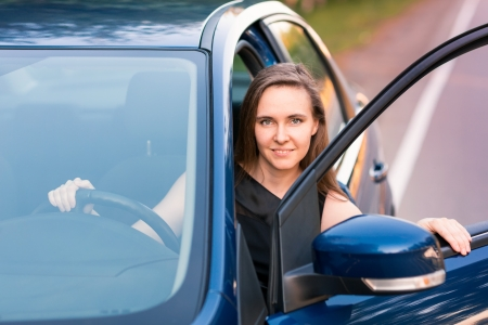 Beautiful happy businesswoman sitting in her car