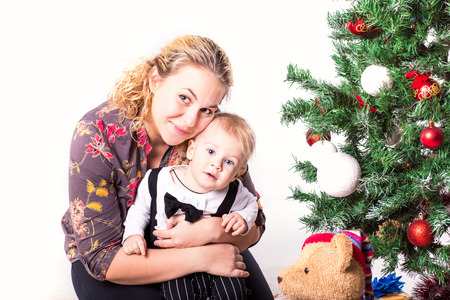 baby near christmas tree: Happy mother and baby near Christmas tree in Santas hat