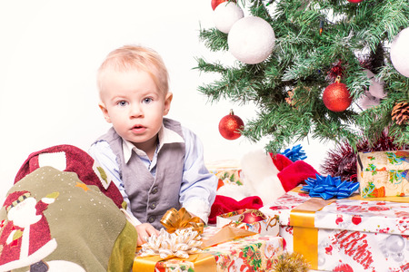 baby near christmas tree: Happy mother and baby near Christmas tree in Santa