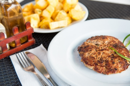 Grilled meat cutlet served with baked potatoes photo