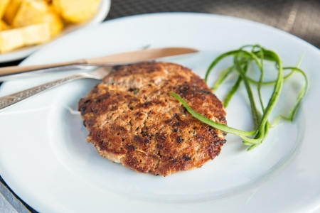 Grilled meat cutlet served on a plate photo