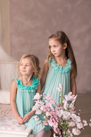 Cute little girls in fashion dresses with spring flowers photo