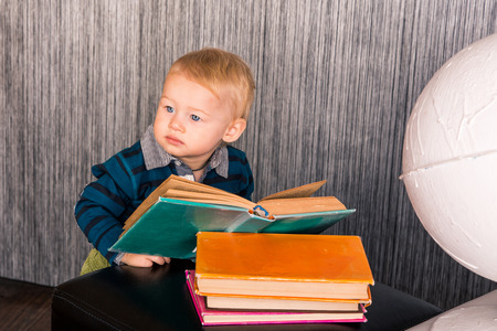 Adorable curious baby boy studying a pile of books indoor photo