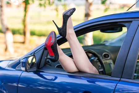 Womans legs in high heel shoes out in a car window outdoor