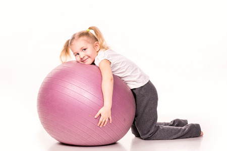 exhilarated: Sportive cute little girl on a fit ball isolated over white