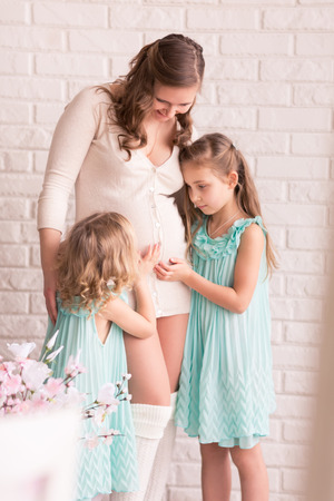 Beautiful pregnant woman with two daughters near the window photo