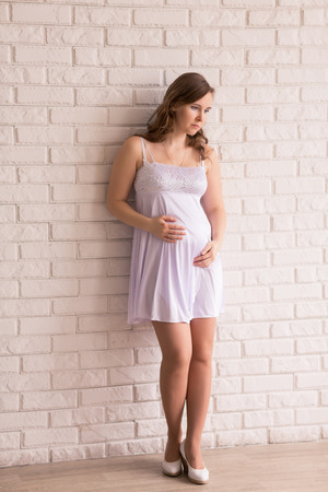 the anticipation: Beautiful pregnant woman in anticipation near the window