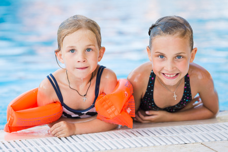 Two cute little girls in swimming pool posing photo