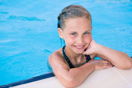 Cute little girl in swimming pool learning how to swim photo
