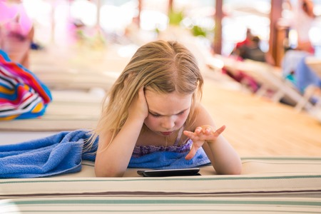 Cute little girl learning with tablet pc on the beach photo