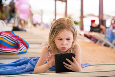 Cute little girl learning with tablet pc on the beach Reklamní fotografie