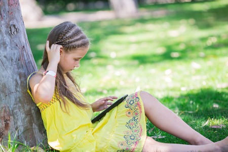 Cute little girl learning with tablet pc in the park photo