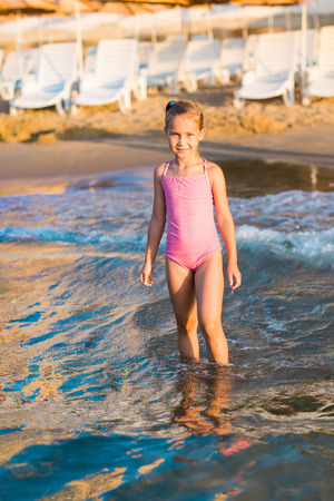 Adorable happy little girl playing in the sea on a beach